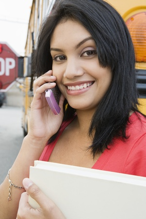 motorcoach: Student Using Cell Phone by School Bus