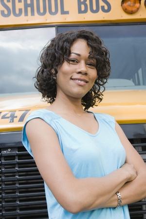 motorcoach: School Teacher in Front of School Bus