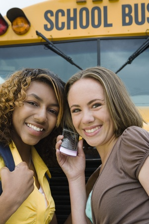 motorbus: High School Girls Listening to Cell Phone by School Bus
