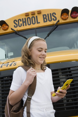 Student Text Messaging by School Bus Stock Photo - 12592952