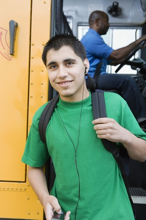 13 year old boy: High School Boy With MP3 Player Getting Off School Bus LANG_EVOIMAGES