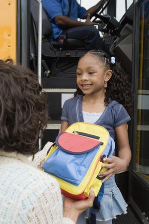 biracial: Mother Handing Daughter Backpack on School Bus LANG_EVOIMAGES
