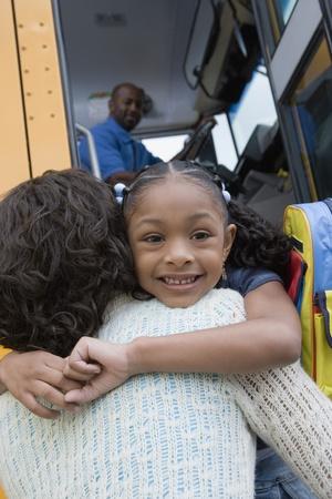 スクールバスの横にある彼女の母親を抱いて少女 写真素材