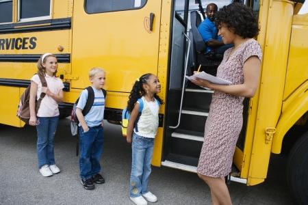 niños saliendo de la escuela: Maestro de carga estudiantes de primaria en el autobús escolar