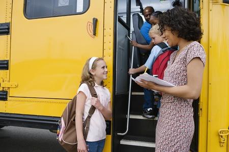 niños de diferentes razas: Maestro de carga estudiantes de primaria en el autobús escolar
