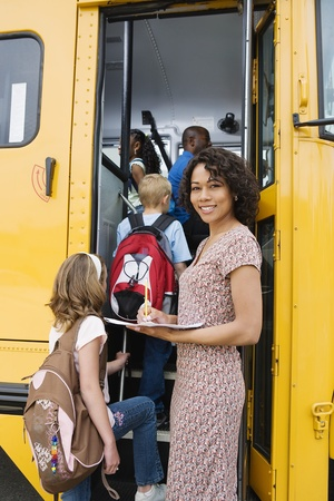 racially diverse: Teacher Loading Elementary Students on School Bus LANG_EVOIMAGES