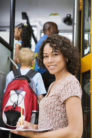先生は学校のバスに小学生の読み込み 写真素材