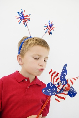Boy Playing with Stars and Stripes Pinwheel Stock Photo - 12736381