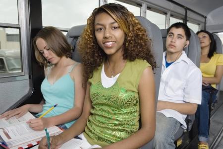 motorbus: Adolescentes haciendo la tarea bien viajar en el autob�s escolar LANG_EVOIMAGES