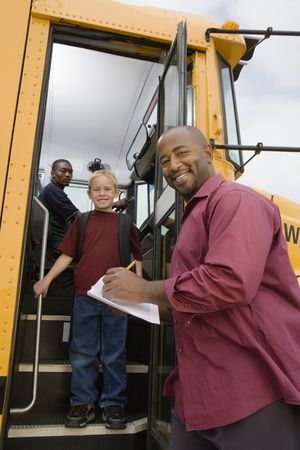 Teacher Unloading Elementary Students from School Bus Stock Photo - 12736406