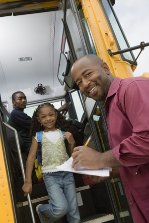 age 25 30 years: Teacher Unloading Elementary Students from School Bus