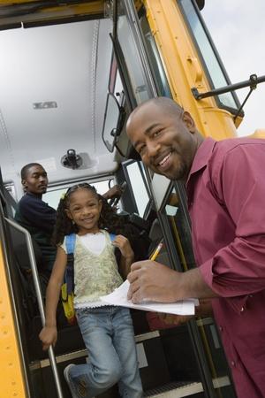 motorcoach: Teacher Unloading Elementary Students from School Bus