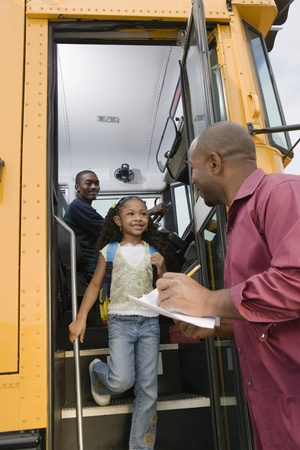 教師学校のバスからアンロード小学生 写真素材