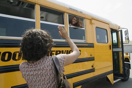 hijos: Madre que agita a la hija adolescente en el autobús escolar LANG_EVOIMAGES