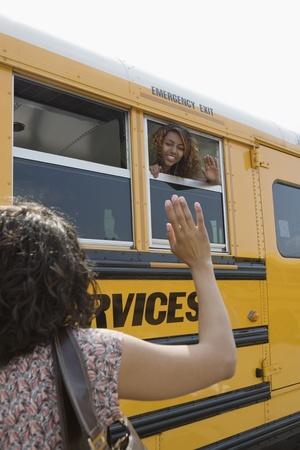 jeune fille adolescente: M�re saluant fille adolescente sur des autobus scolaires