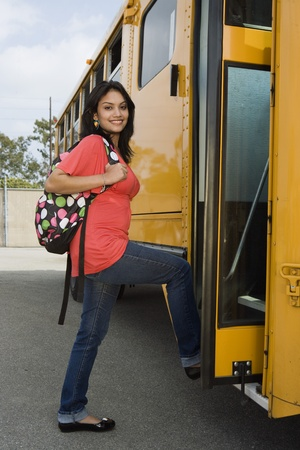 Teenage Girl Getting on School Bus Stock Photo
