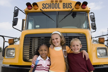 racially diverse: Elementary Students Standing by School Bus