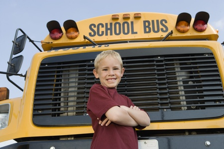 motorcoach: Elementary Student Standing by School Bus LANG_EVOIMAGES