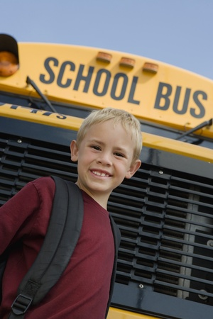 motorbus: Elementary Student Standing by School Bus LANG_EVOIMAGES