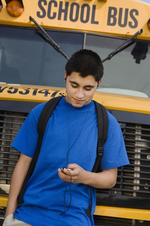 13 year old boy: Teenager Boy Listening to MP3 Player by School Bus LANG_EVOIMAGES