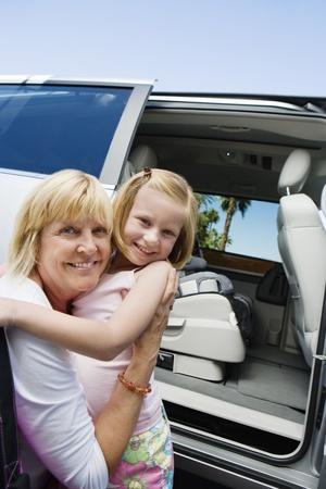 45 to 50 years old: Mother Hugging Daughter by Minivan