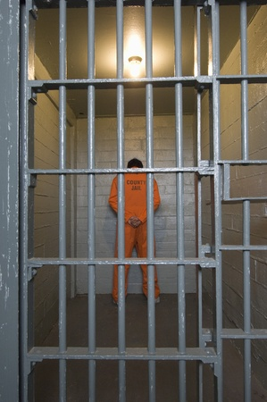 Prisoner standing in prison cell Stock Photo - 12736461