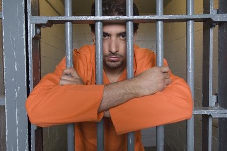 prison system: Portrait of prisoner behind bars LANG_EVOIMAGES