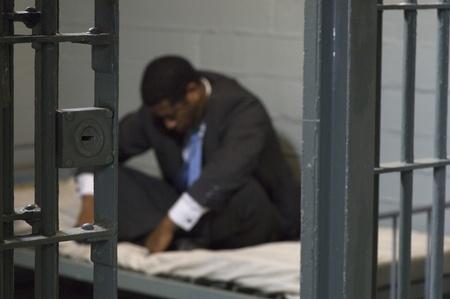 prison system: Businessman in prison cell