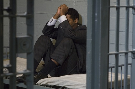Businessman sitting on bed in prison cell Stock Photo - 12736467