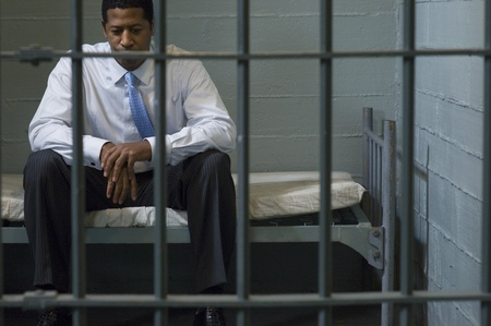 prison system: Businessman sitting in prison cell