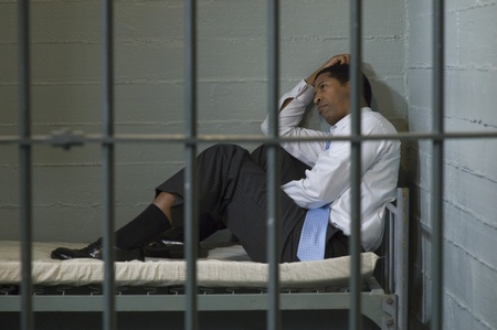 prison system: Mature man sitting on bed in prison cell