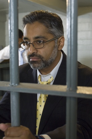 Man in spectacles behind bars Stock Photo - 12736478