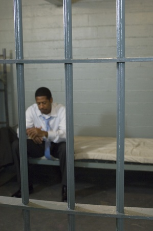Man sitting in prison cell Stock Photo - 12736480
