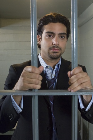 Man standing behind cell bars Stock Photo - 12736482
