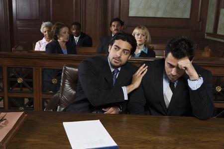 Deux hommes assis devant un tribunal