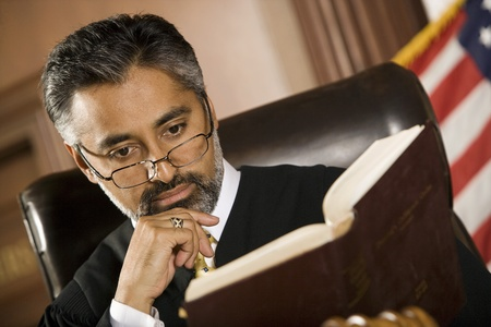 Middle-aged judge reading in a courtroom Stock Photo - 12736667