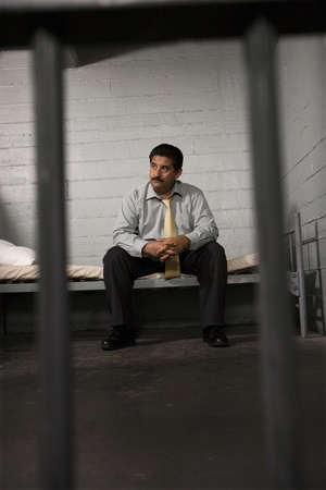 Criminal sitting on bed in jail Stock Photo - 12736695