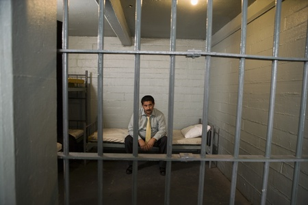 Criminal sitting on bed in jail Stock Photo - 12736696