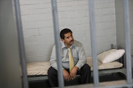 Criminal sitting on bed in jail Stock Photo - 12736698