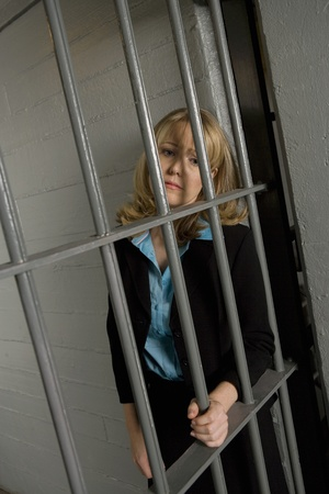 Female criminal behind bars in jail Stock Photo - 12736702