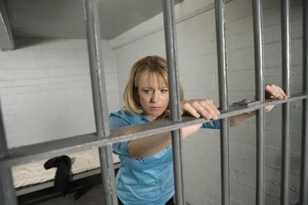 prison system: Female criminal behind bars in jail