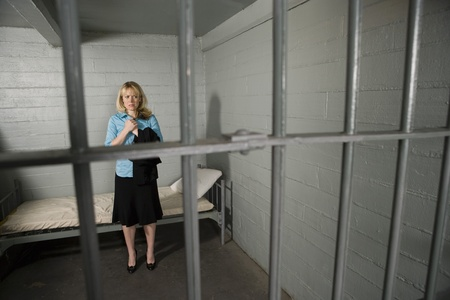 Female criminal behind bars in jail Stock Photo - 12736705