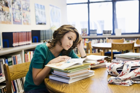 only teenage girls: High School Student Reading in Library LANG_EVOIMAGES