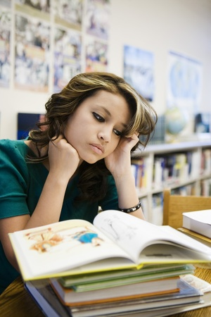 16 to 17 year olds: High School Student Reading in Library LANG_EVOIMAGES