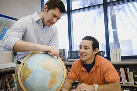 17 year old: High School Teacher Pointing out Location on Globe to Student
