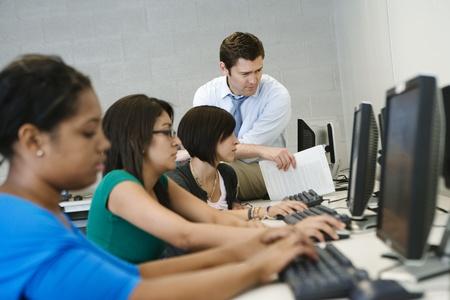 教師を助力学生のコンピューター室で