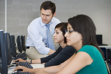 Teacher Helping Computer Students Stock Photo - 12736852