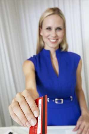 salespeople: Saleswoman Handing Credit Card back to Customer LANG_EVOIMAGES
