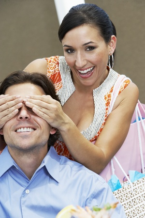 Woman Holding Hands over Man's Eyes Stock Photo - 12736955