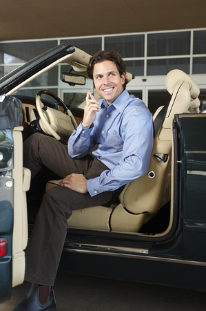 Man Sitting in a Convertible Talking on a Cell Phone Stock Photo - 12736985